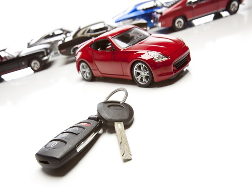 Car Keys and Several Sports Cars on White Background.